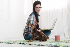 Маленькая девочка на поле с компьтер-книжкой и собакой Стоковые Фотографии RF
