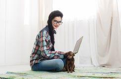 Маленькая девочка на поле с компьтер-книжкой и собакой Стоковая Фотография