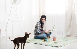 Маленькая девочка на поле с компьтер-книжкой и собакой Стоковые Изображения