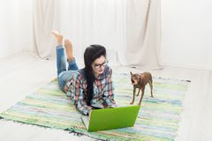 Маленькая девочка на поле с компьтер-книжкой и собакой Стоковое Изображение RF