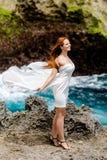Маленькая девочка на скале перед океаном стоковое фото rf