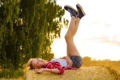 Маленькая девочка на снопах соломы в поле Стоковые Фото
