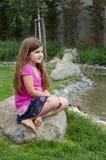 Маленькая девочка на утесе штилевым потоком Стоковые Изображения
