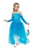 Маленькая девочка нося голубое платье шарика в полнометражном делая реверансе стоковое фото rf