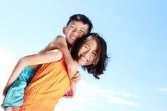 Маленькая девочка нося ее брата стоковое изображение rf