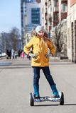 Маленькая девочка нося желтую куртку стоя на само-сбалансированном gyroscooter на городской улице Стоковое фото RF