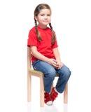 Маленькая девочка нося красная t-короткую и представляя на стуле Стоковое Изображение