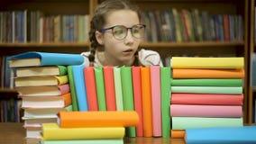Маленькая девочка обнимает стог книг на предпосылке полок с книгами акции видеоматериалы