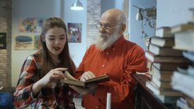 Маленькая девочка обсуждает книгу с дедом сток-видео
