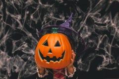 Маленькая девочка одетая как ведьма держа тыкву против темной предпосылки с spiderwebs Стоковые Изображения