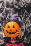 Маленькая девочка одетая как ведьма держа тыкву против темной предпосылки с spiderwebs Стоковое Изображение