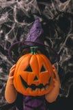 Маленькая девочка одетая как ведьма держа тыкву против темной предпосылки с spiderwebs Стоковые Изображения RF