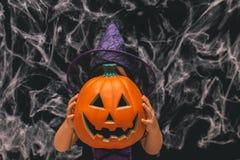 Маленькая девочка одетая как ведьма держа тыкву против темной предпосылки с spiderwebs Стоковая Фотография RF