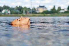 Маленькая девочка ослабляя путем плавать на задней части в русском пригородном озере на летних каникулах стоковая фотография