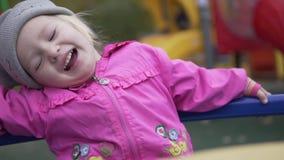 Маленькая девочка отбрасывающ и смеющся над весело сток-видео
