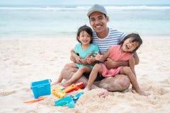 Маленькая девочка 2 отца обнимая от за сидя стоковые фотографии rf