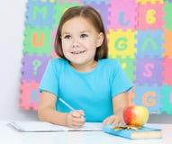 Маленькая девочка пишет используя пер стоковые изображения
