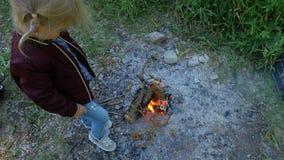 Маленькая девочка подготавливает хлеб на коле Ребенок около огня в кампании видеоматериал