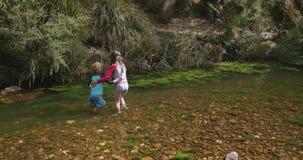 Маленькая девочка поддерживает ее молодого брата по мере того как они идут колено глубоко в воде в реке сток-видео