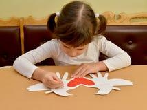 Маленькая девочка подписывает карточку дня ` s валентинки карточки подарка с голубями Стоковые Изображения