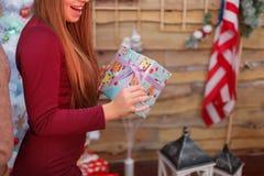 Маленькая девочка показывает ее подарочную коробку Атмосфера рождества indoors стоковая фотография