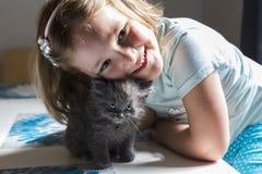 Маленькая девочка полагаясь над ее прелестным голубоглазым крошечным серым котенком стоковое фото rf