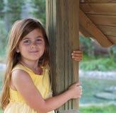 Маленькая девочка полагаясь на столбе Стоковые Изображения