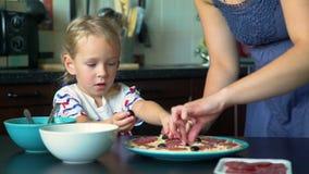Маленькая девочка положила оливки на основание пиццы видеоматериал