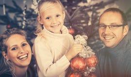 Маленькая девочка помогая ее семье украшая рождественскую елку стоковая фотография rf