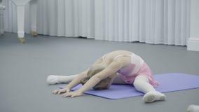 Маленькая девочка помощи учителя студии танца делает заднюю часть загиба внутри акции видеоматериалы