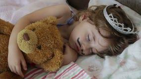 Маленькая девочка портрета конца-вверх спать в кровати девушка с кроной принцессы на ее голове в кровати обнимая игрушку плюшевог акции видеоматериалы