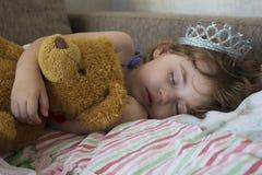 Маленькая девочка портрета конца-вверх спать в кровати девушка с кроной принцессы на ее голове в кровати обнимая игрушку плюшевог стоковое изображение