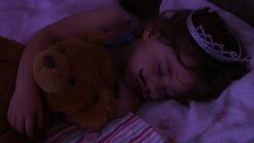 Маленькая девочка портрета конца-вверх спать в кровати девушка с кроной принцессы на ее голове в кровати обнимая игрушку плюшевог сток-видео