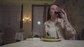 Маленькая девочка портрета милая есть красиво служила лапши аппетита с arugula выпивая красное вино и улыбку к кто-то акции видеоматериалы