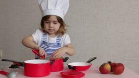 Маленькая девочка портрета прелестная в еде кашевара шляпы шеф-повара видеоматериал