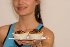 Маленькая девочка предлагает свеже испеченную булочку с плодоовощ Стоковое Изображение