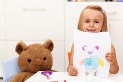 Маленькая девочка представляет ее чертеж - портрет ее медведя игрушки Стоковое Изображение