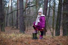 Маленькая девочка представляя около старого пня в лесе осени Стоковая Фотография RF
