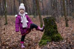 Маленькая девочка представляя около старого пня в лесе осени Стоковое Изображение
