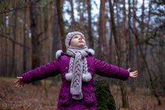 Маленькая девочка представляя около старого пня в лесе осени Стоковое Фото