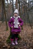 Маленькая девочка представляя около старого пня в лесе осени Стоковая Фотография