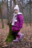 Маленькая девочка представляя около старого пня в лесе осени Стоковые Фото