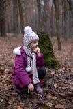 Маленькая девочка представляя около старого пня в лесе осени Стоковые Фотографии RF