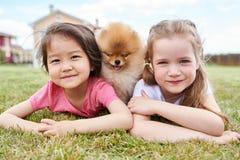 Маленькая девочка представляя с щенком стоковое изображение