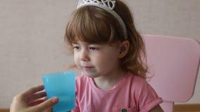 Маленькая девочка принимает медицину пилюльки и выпивает с водой Закройте вверх по больному ребенку принимает пилюльку медицины видеоматериал