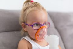 Маленькая девочка принимает терапию вдыхания стоковое фото rf