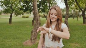 Маленькая девочка принимансяа за прогулке в парке, смотря умные часы на ее руке и получая измерение ИМПа ульс видеоматериал