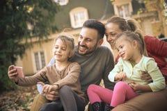 Маленькая девочка принимая автопортрет с всей семьей Стоковое Фото