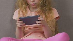 Маленькая девочка пристрастившийся к smartphone, не может остановить использовать мобильное устройство, зависимость сток-видео