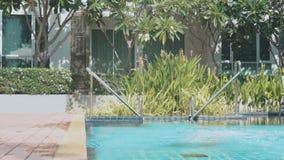 Маленькая девочка приходя к бассейну и скача в воду в замедленном движении сток-видео